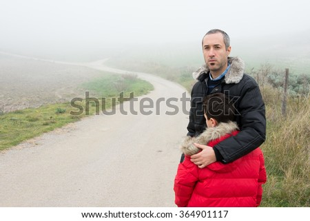 Concept of family escaping.  Father and son in a mountain road with fog. Scene with actors - stock photo