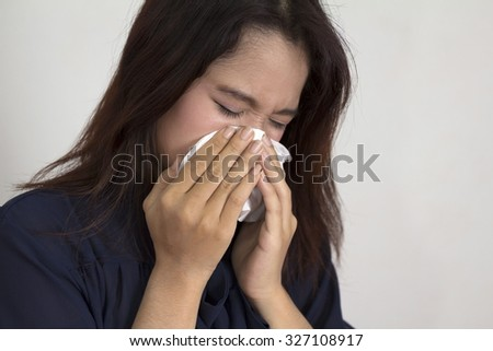 Concept of flu illness with Young woman holding tissue and runny nose - stock photo