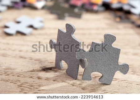 Concept of friendship:closeup of two jigsaw puzzle pieces on table. Shallow depth of field - stock photo