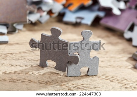 Concept of friendship: closeup of two jigsaw puzzle pieces on table. Shallow depth of field - stock photo