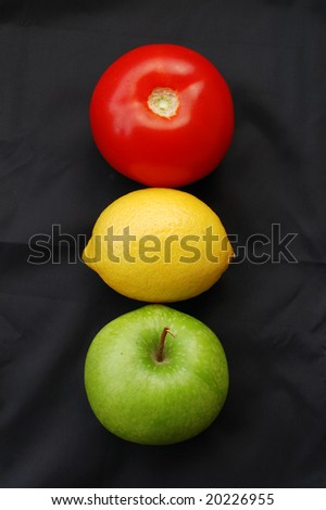 Concept of fruits representing traffic light on black background (red = stop, yellow = caution, green = go) - stock photo