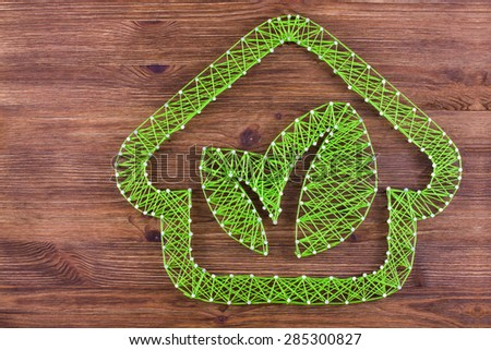 Concept of green eco-friendly house on wooden background. Handmade string art.  - stock photo