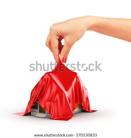 Concept of house. Woman hand take off red cloth from house. - stock photo