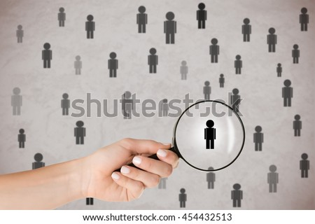 Concept of Human Resources selection. Hand holding loupe selecting a candidate. - stock photo
