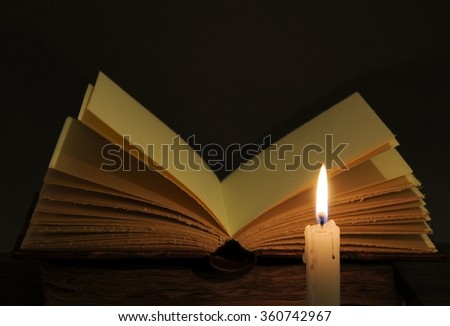 Concept of knowledge. Open book and candle. - stock photo