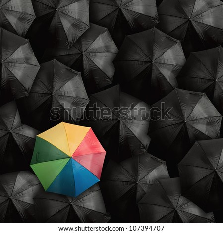 Concept of leader with with many blacks and a colorful umbrella - stock photo