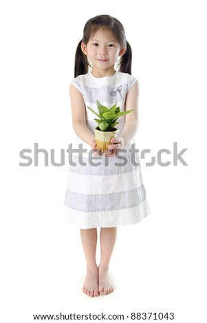 Concept of little girl holding a plant on white background - stock photo