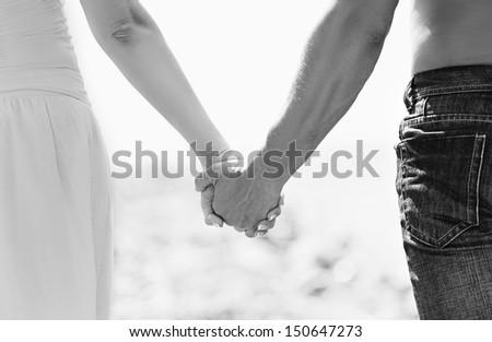 concept of love and family. the hands of lovers, men and women in monochrome - stock photo