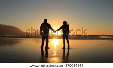 Concept of love and happiness. Silhouette of a romantic couple holding hands on the beach at Cape Town city, South Africa. Man and woman enjoying sunset on beach. - stock photo