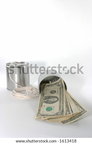 Concept of money to be made in supporting old technology. Front view of telephones made out of tin cans and a string, emphasis on one side's tin can. - stock photo