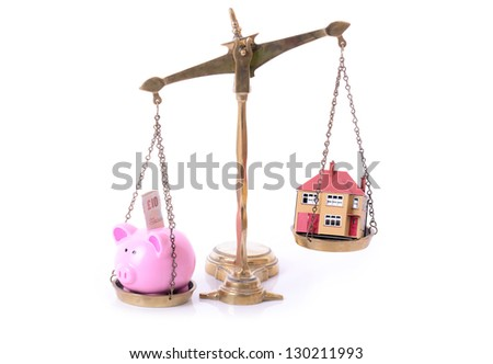 concept of mortgage and saving piggy bank and house on scales - stock photo