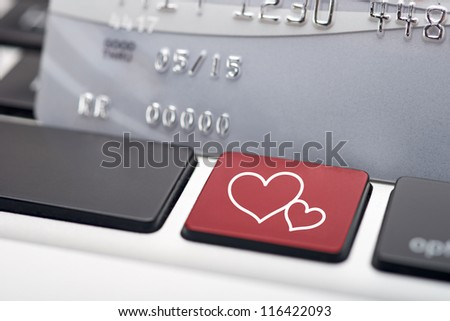 Concept of online dating with keyboard and credit card - stock photo