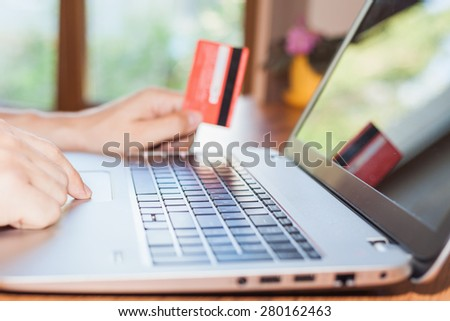 Concept of online payment by plastic card through the Internet Banking. Close-up of human hand for laptop and holding credit card, man is shopping indoor at home - stock photo