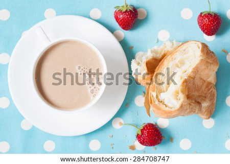 Concept of perfect lunch or breakfast. A cup of coffee latte with a piece of traditional French croissant pasrty and fresh strawberries on provence style background. Rustic style and natural light. - stock photo