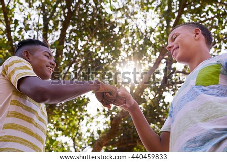 Concept of racism and integration. Black and white boys meeting and joining hands - stock photo
