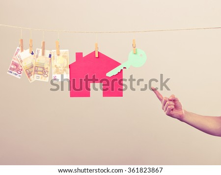 Concept of real estate and deal. Hand of seller man with house model and money banknotes. Selling and buying proposition. - stock photo