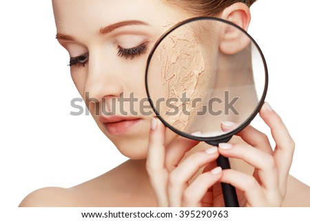 concept of rejuvenation and skin care. face of a beautiful girl with a problem skin and magnifier - stock photo