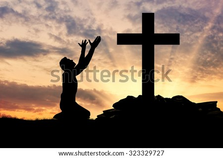 concept of religion. Silhouette of a man praying before a cross at sunset - stock photo