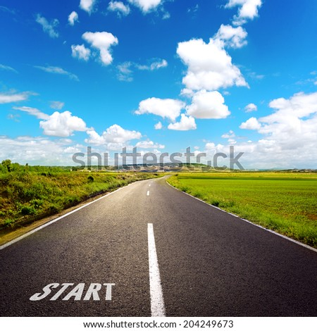 Concept of right path to progress and success. Beautiful straight asphalt road among green grass with blue sky background.  - stock photo