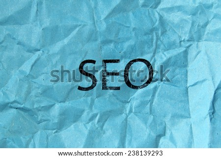 concept of SEO word on blue crumpled paper - stock photo