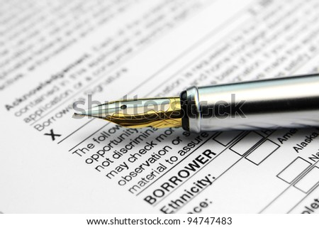 Concept of signing loan agreement with shiny pen - stock photo