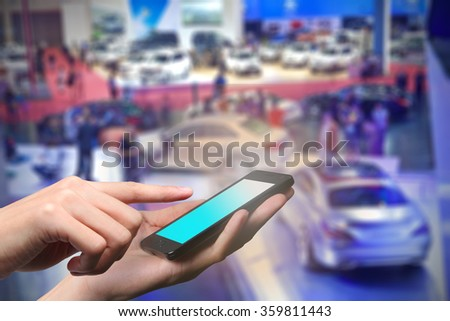 Concept of smart phone using in hall event of motor show Closed up hand of man touch screen. - stock photo