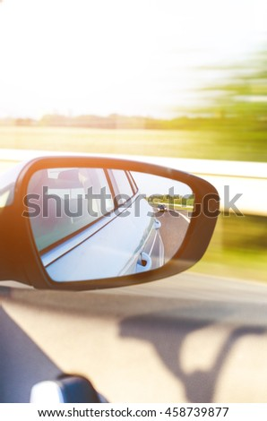 Concept of speed. Car driving on the road. Reflection in a car mirror.Rear view mirror reflection. Blurry background. - stock photo