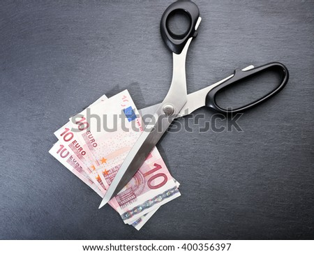 Concept of spending money - scissors cut money on black background - stock photo