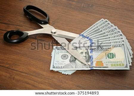 Concept of spending money - scissors cut money on wooden background - stock photo