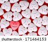 Concept of standing out from the crowd. Pink heart with smiley face between a pile of white hearts with sad faces. Candy Hearts background - stock photo