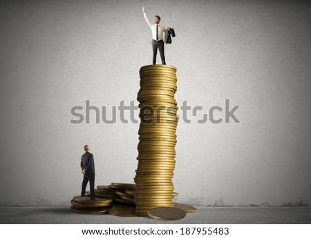 Concept of successful businessman on top of a stack of coins - stock photo