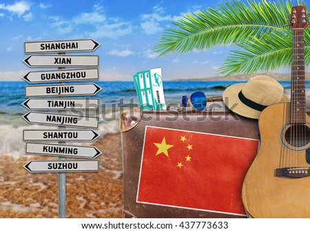 Concept of summer traveling with old suitcase and China town sign - stock photo