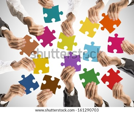 Concept of teamwork and integration with businessman holding colorful puzzle - stock photo