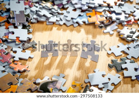 Concept of teamwork: Three jigsaw puzzle pieces on a table. Shallow depth of field - stock photo