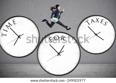 Concept of time for taxes with a businesswoman running on watch - stock photo