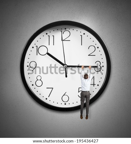 Concept of time with a businessman hanging from the hands of a clock - stock photo