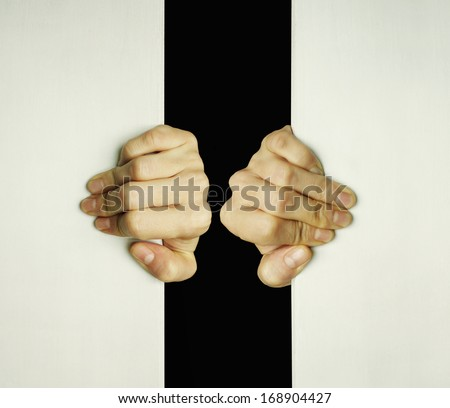 Concept of two hands trying to open a slit to exit from the darkness - stock photo