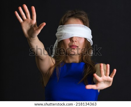Concept of uncertainty, blindness or helplessness: portrait of young lost woman (girl) with white bandage on eyes and arms outstretched looking or searching for something in darkness. - stock photo