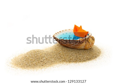 concept of vacation rest, origami boat floating in blue water in shell on heap of sand - stock photo