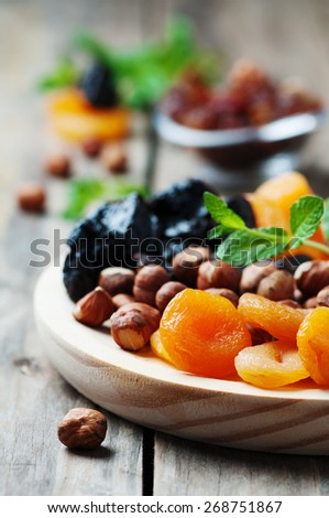 Concept of vegan dessert with dry apricots, plums, raisins and nuts, selective focus - stock photo