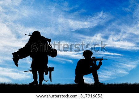 Concept of war. Silhouette of a soldier carries a wounded soldier on a background of sky - stock photo