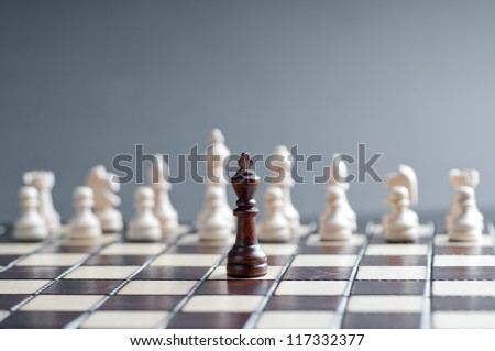 concept of wooden chess. one black chess against white - stock photo