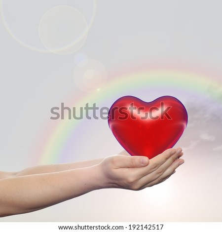 Concept or conceptual 3D red glass heart sign or symbol held in hands by a woman or child over nice rainbow sky background, metaphor to love, holiday, wedding, care, valentine, protection or romantic - stock photo