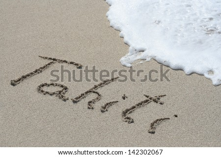 Concept or conceptual hand or handwritten Tahiti text in sand on beach in exotic island as metaphor to summer,ocean,sea,travel,vacation,tourism,tropical,coast,message,resort,paradise,sunny or water - stock photo