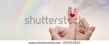 Concept or conceptual human or female hands with two fingers painted with a red heart and smile faces over rainbow sky background for valentine, romantic, love, couple, young, family wedding banner - stock photo