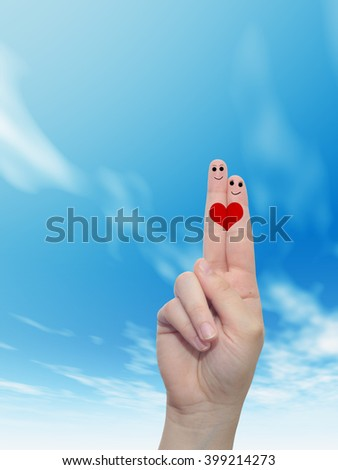 Concept or conceptual human or female hands with two fingers painted with a red heart and smiley faces over cloud blue sky background for valentine, romantic, love, couple, young, family or wedding - stock photo