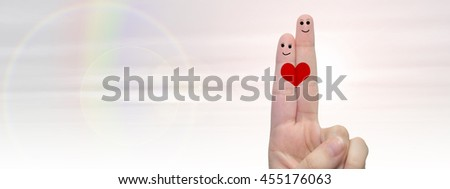 Concept or conceptual human or female hands with two fingers painted with a red heart and smiley faces over rainbow sky background banner for valentine, romantic, love, couple, young, family wedding - stock photo