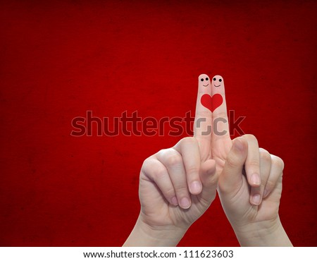 Concept or conceptual human or female hands with two fingers painted with a red heart over a old vintage paper background for valentine,romantic, love,couple,young,family or wedding - stock photo