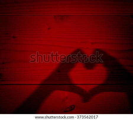 Concept or conceptual Valentine human man and woman hands silhouette as heart or love symbol on old red wood background - stock photo