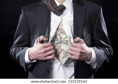 Concept photo for hidden money showing a businessman pulling back his shirt exposing twenty dollar bills - stock photo